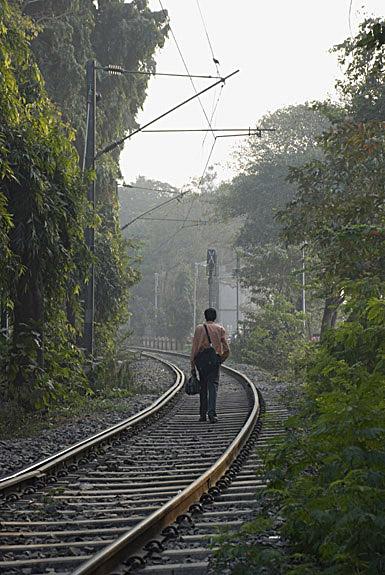A man walking on a railway track  ,  India