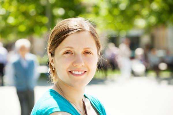Outdoor portrait of smiling woman in sunny day