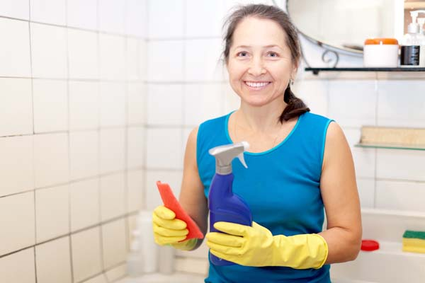 mature woman cleans bathroom with sponge