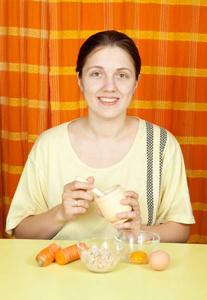 woman making face-pack from carrot, oatmeal and egg yolk