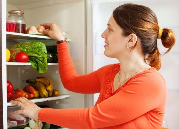 Young housewife near refrigerator at home