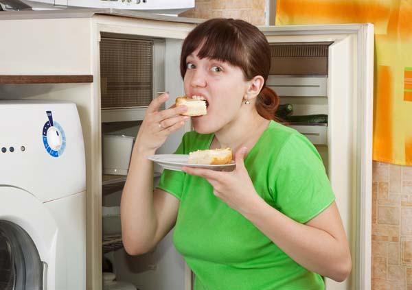 Young woman near opening fridge eating pie