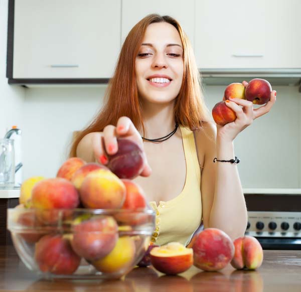 Happy pretty woman with peaches in home kitchen