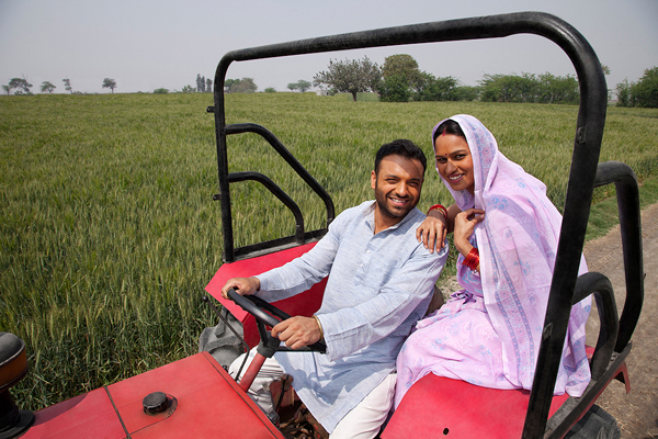 Portrait of an Indian couple sitting in a tractor with field in background