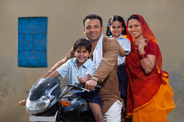 Portrait of a happy Indian family of four on bike