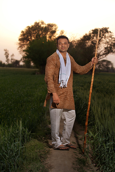 Full length of an Indian farmer standing with a stick