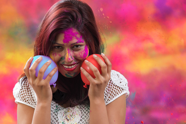 Indian Happy Young Girl With Holi Balloons at Holi Festival