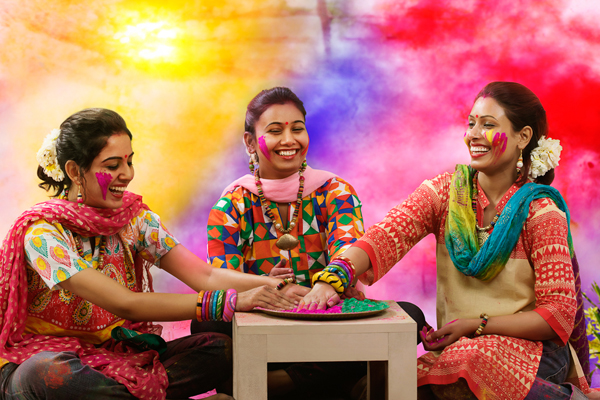 Three teenage Indian girls celebrating Holi festival with traditional dresses and ornaments