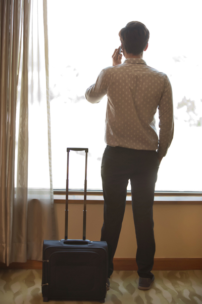 Rear view of man standing near window talking on phone with trolley bag