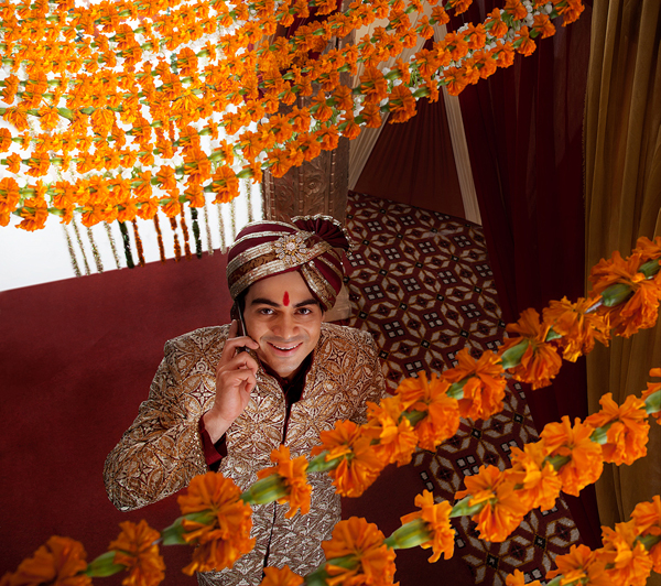 Young Indian bridegroom talking on mobile phone while looking up