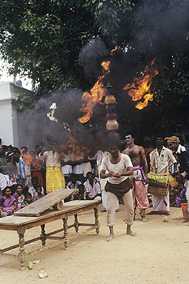 Man balancing fire kept at the apex supported by series of six pots during the Pongal Festival ,   Tamil Nadu  ,   India
